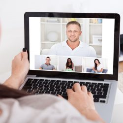 Cropped image of young woman using laptop for video conference at home