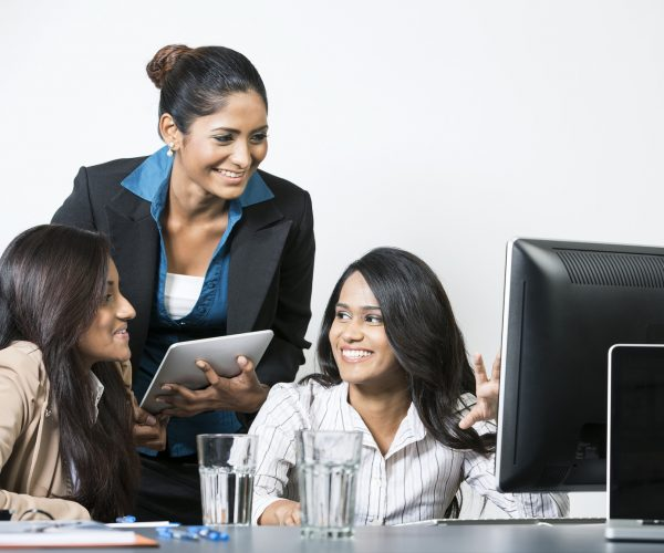 Happy Indian business women working on an assignment.