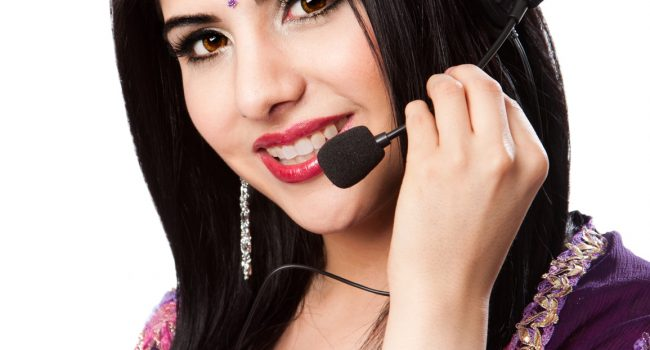 Beautiful Happy Indian Hindu Business Customer Service Representative at call center with headset microphone, isolated.